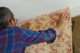 Man applying wallpaper